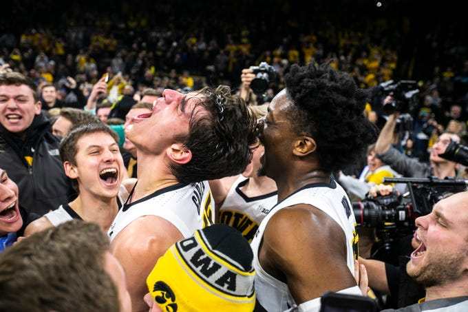 Iowa forward Luka Garza (55) celebrates with Iowa guard Austin Ash, left, and Tyler Cook, right, during a NCAA Big Ten Conference men's basketball game on Friday, Feb. 1, 2019, at Carver-Hawkeye Arena in Iowa City, Iowa. The Hawkeyes defeated Michigan's Wolverines, 74-59.