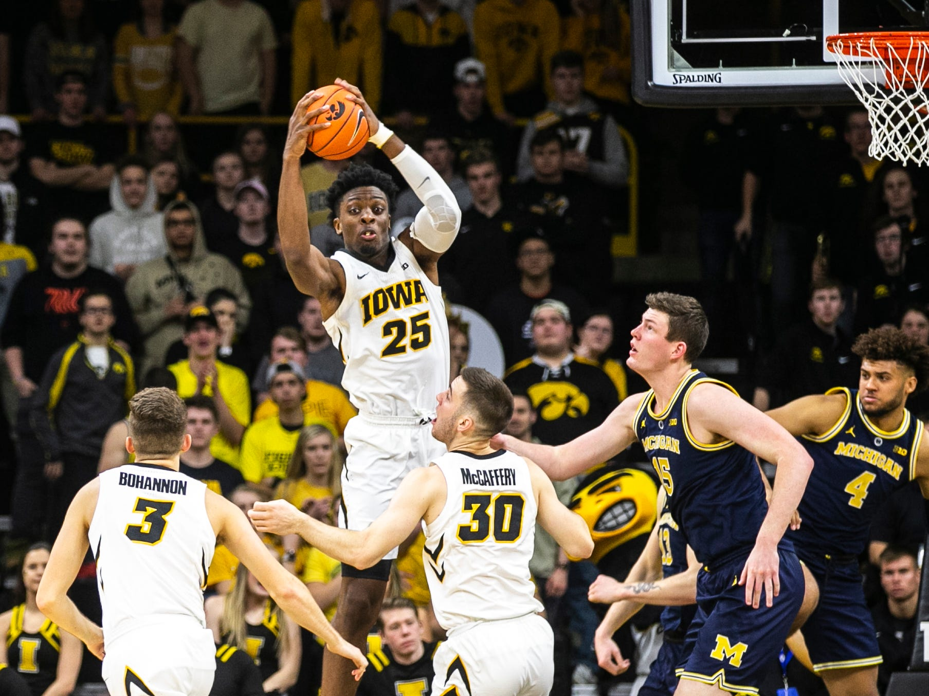 Iowa forward Tyler Cook (25) grabs a rebound away from Michigan forward Ignas Brazdeikis (13) during a NCAA Big Ten Conference men's basketball game on Friday, Feb. 1, 2019, at Carver-Hawkeye Arena in Iowa City, Iowa.
