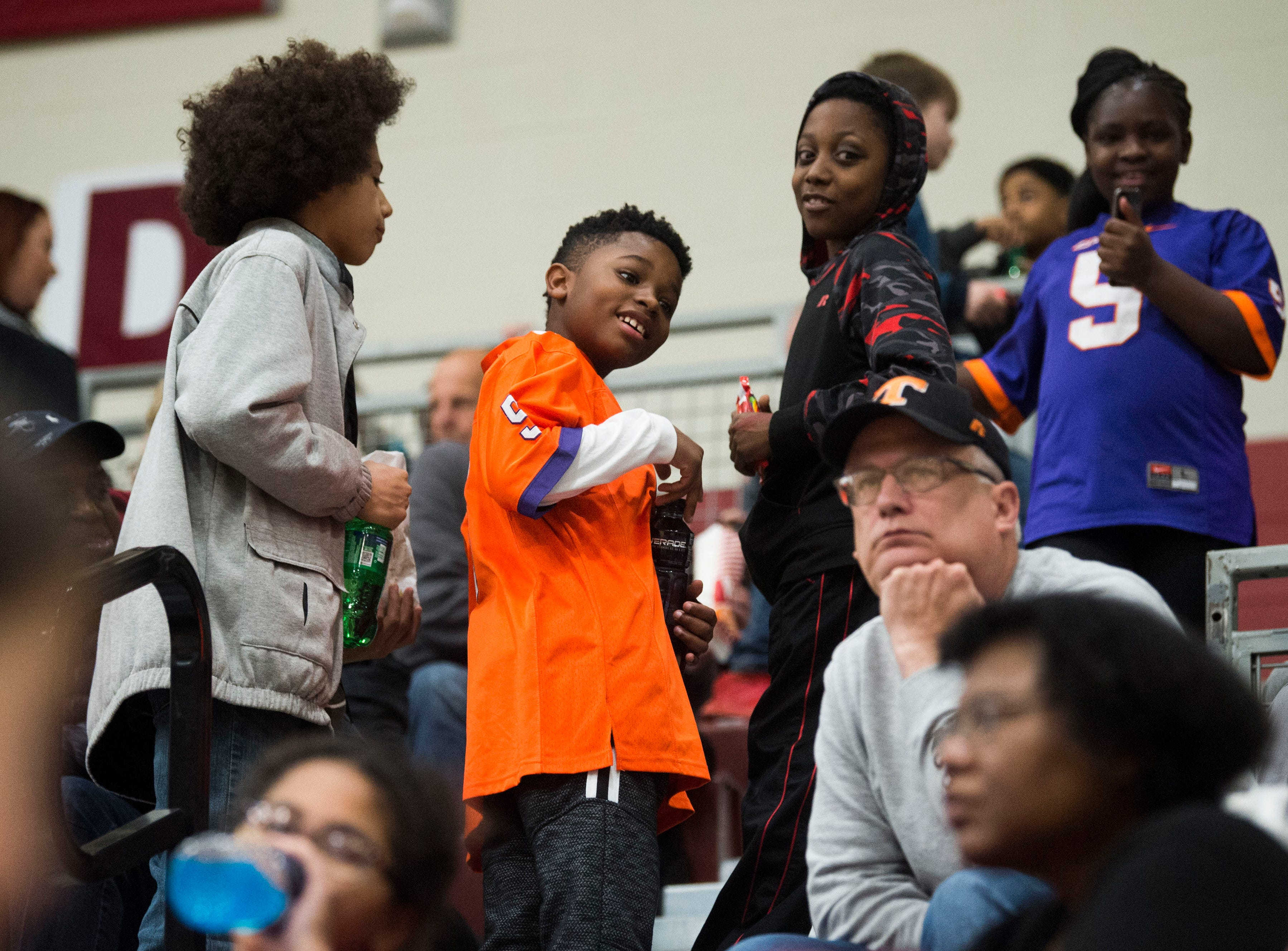 At center Tyree Porter, 11, and to his right Ja-Rel Jemerson 11, hang out with friends in the bleachers during a high school basketball game between Oak Ridge and Campbell County at Oak Ridge Friday, Feb. 1, 2019.
