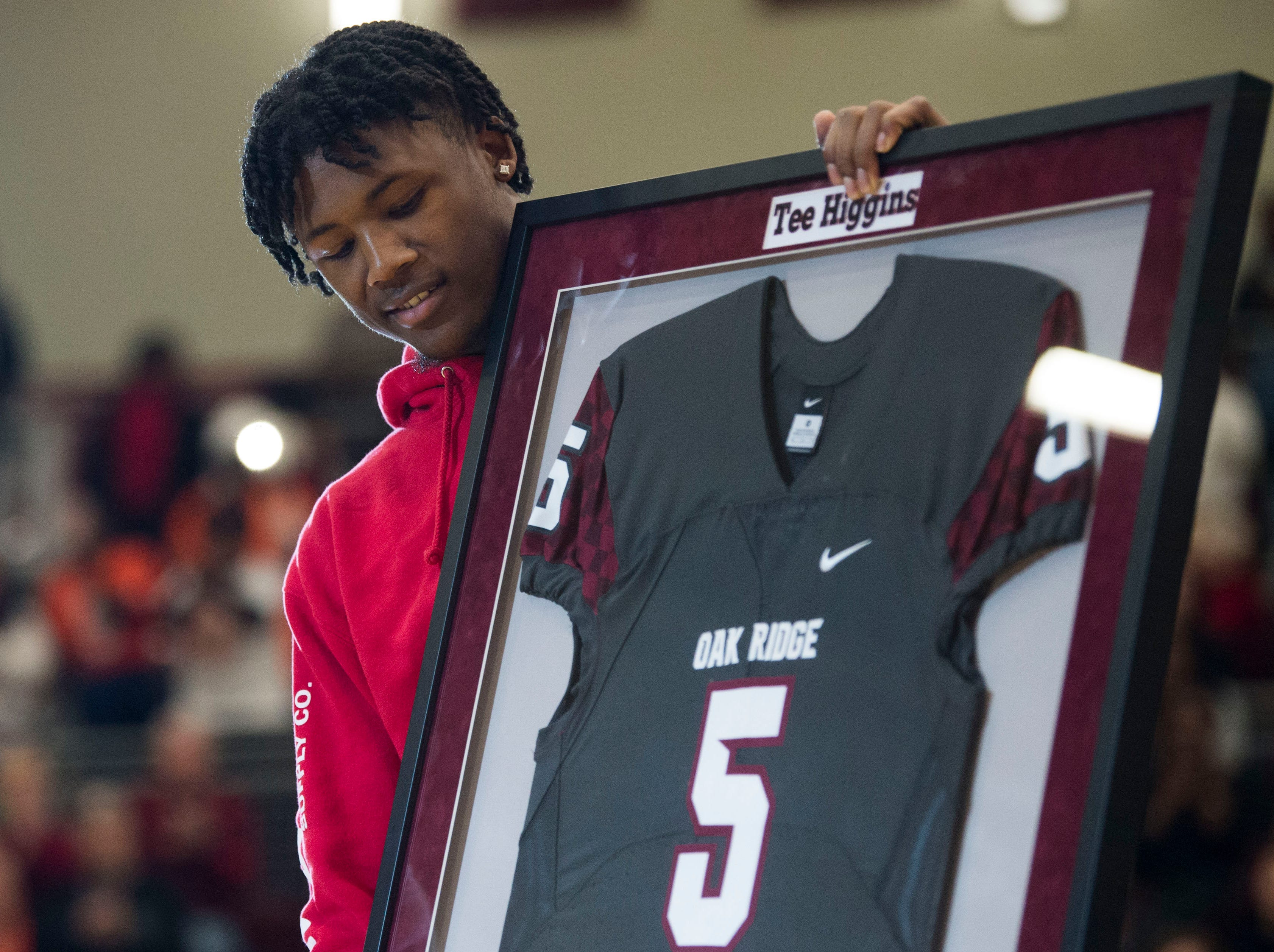 Former Oak Ridge High School athlete Tee Higgins, now a wide receiver at Clemson University, holds up his jersey as it is retired, during a high school basketball game between Oak Ridge and Campbell County at Oak Ridge Friday, Feb. 1, 2019.