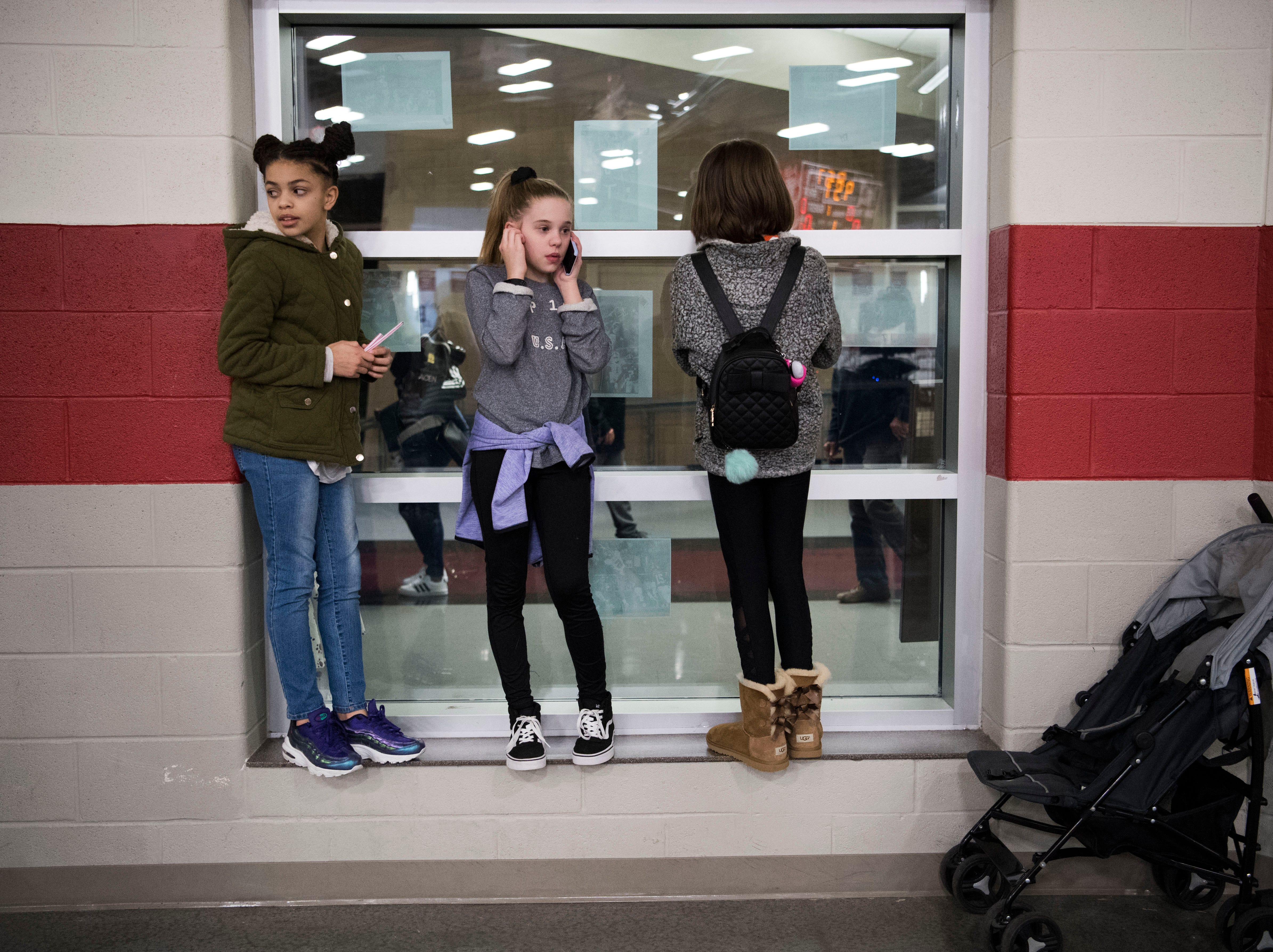 Friends pass time during a high school basketball game between Oak Ridge and Campbell County at Oak Ridge Friday, Feb. 1, 2019.