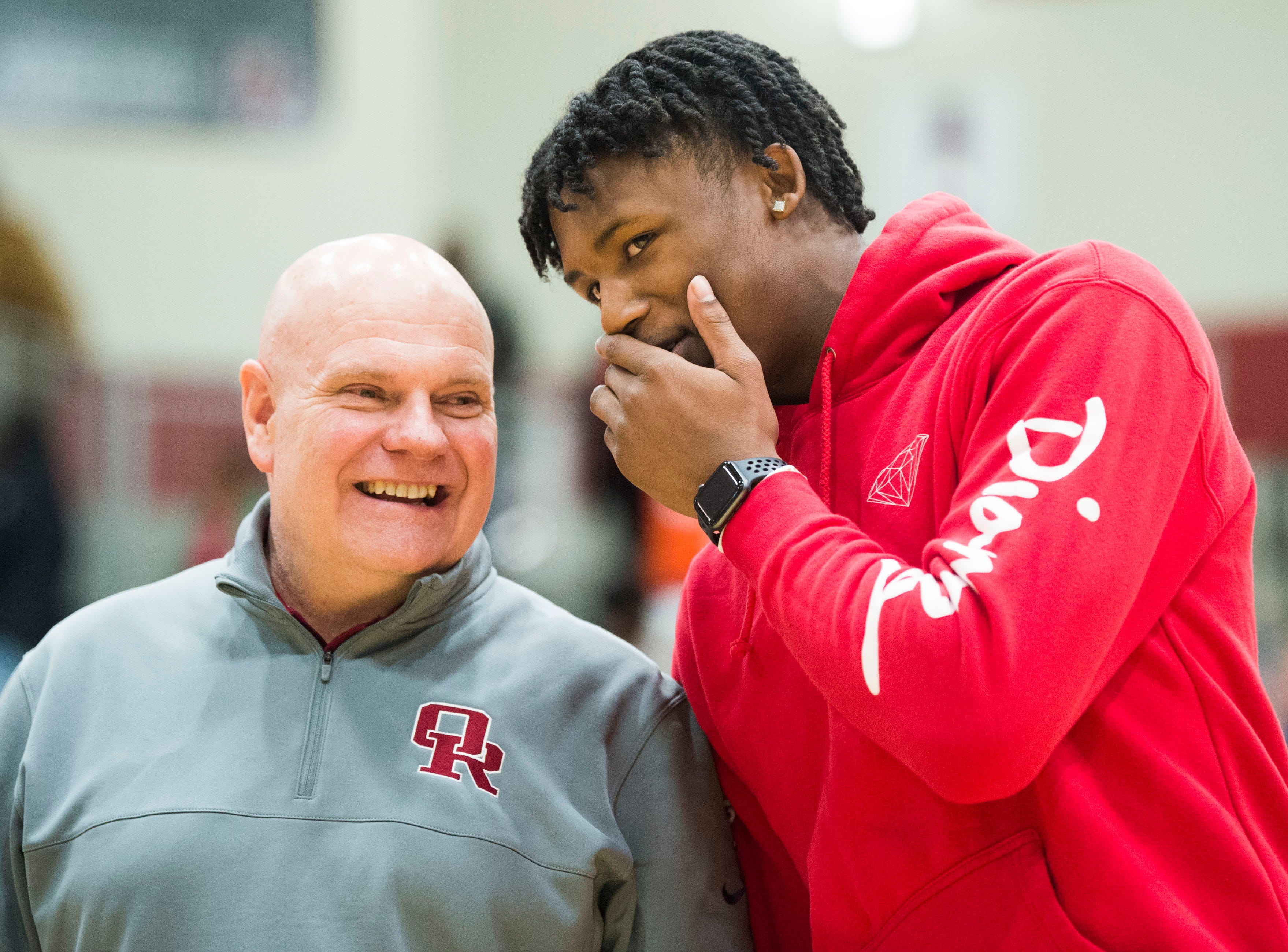 From left Oak Ridge High School athletic director Mike Mullins listens as former Oak Ridge High School athlete Tee Higgins, now a wide receiver at Clemson University, whispers to him, as Higgin's jersey is retired during a high school basketball game between Oak Ridge and Campbell County at Oak Ridge Friday, Feb. 1, 2019.
