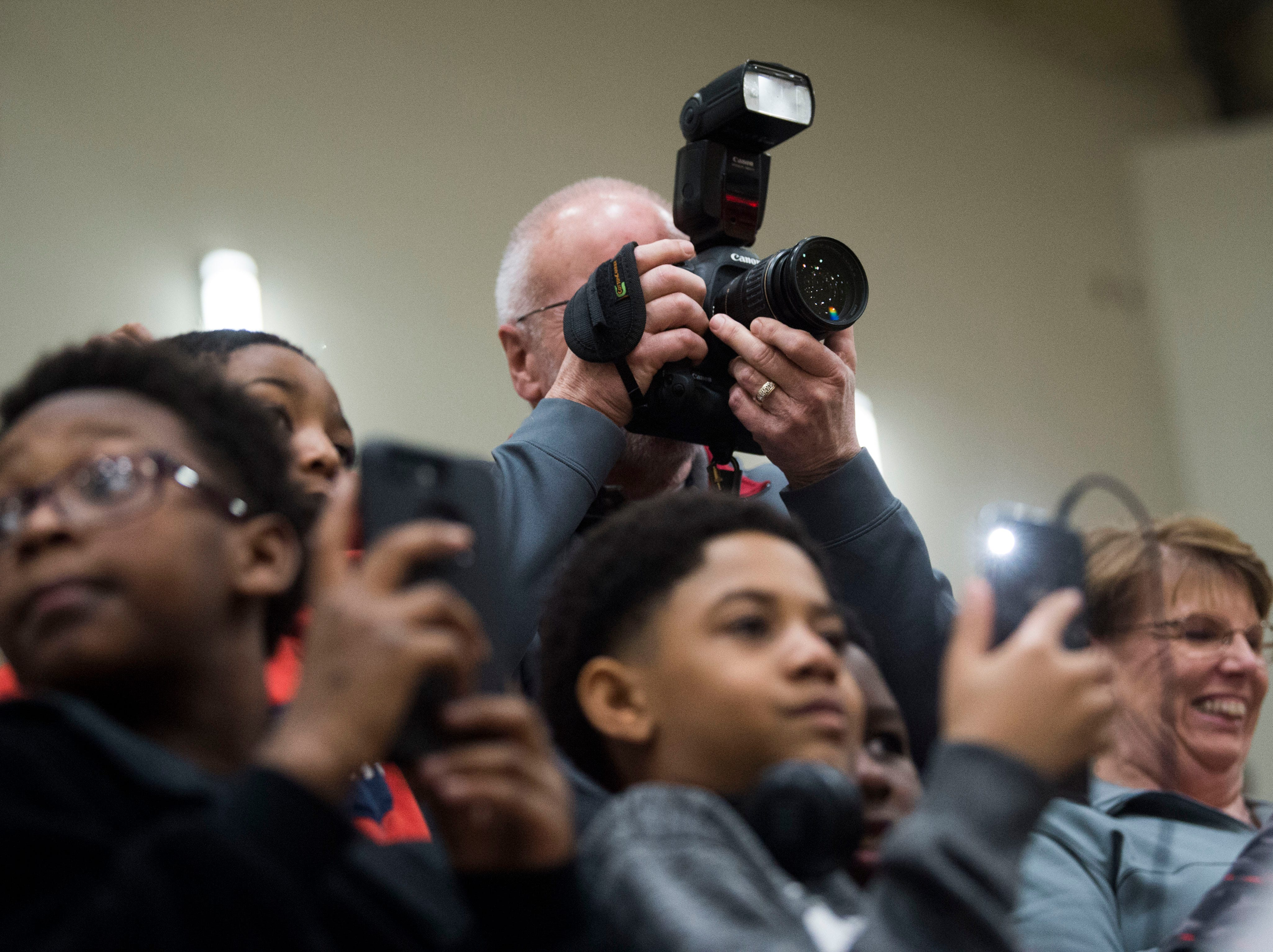 Attendees film former Oak Ridge High School athlete Tee Higgins, now a wide receiver at Clemson University, as he returns to the court for his jersey to be retired, during a high school basketball game between Oak Ridge and Campbell County at Oak Ridge Friday, Feb. 1, 2019.