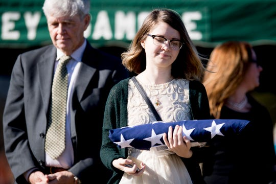 Emmalee Mariner, daughter of Rosemary Mariner, the US Navy's first female fighter pilot, carries the burial flag as her father, Tommy Mariner, seen in background, follows after a graveside service at New Loyston Cemetery in Maynardville, Tennessee on Saturday, February 2, 2019. Mariner died January 24th of cancer.