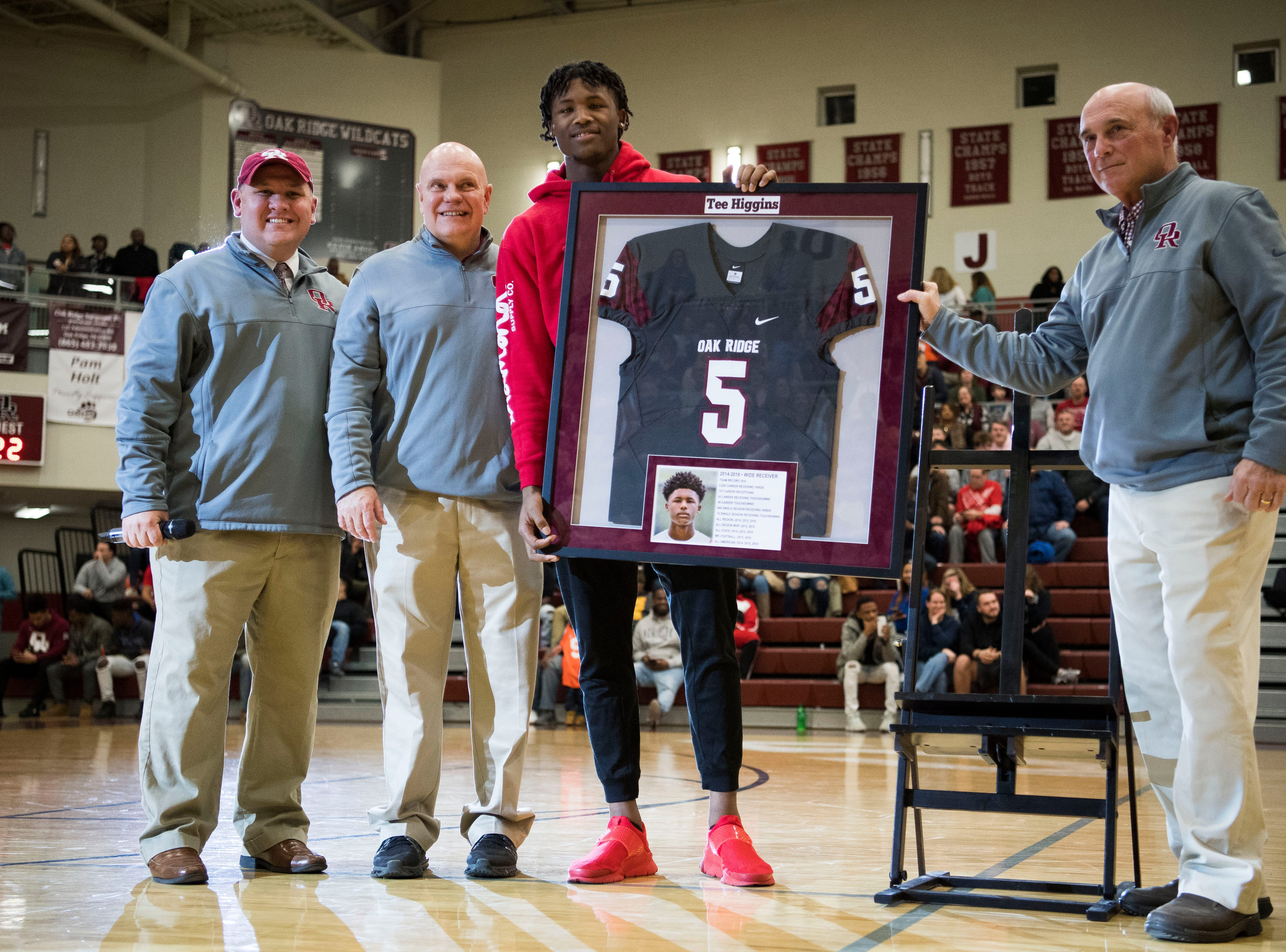 From left Oak Ridge High School principal Martin McDonald, ORHS athletic director Mike Mullins, former Oak Ridge High School athlete Tee Higgins, who is now a wide receiver at Clemson University, and ORHS head football coach Joe Gaddis, pose for a photo as Higgin's jersey is retired during a high school basketball game between Oak Ridge and Campbell County at Oak Ridge Friday, Feb. 1, 2019.
