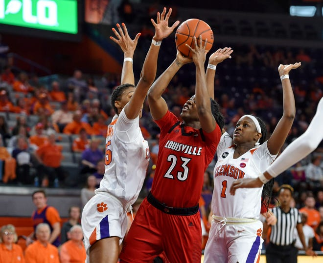Louisville's Jazmine Jones (23) shoots while pressured by Clemson's Tylar Bennett, left, and Destiny Thomas during the first half of an NCAA college basketball game Saturday, Feb. 2, 2019, in Clemson, S.C.