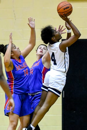 Eastern's Ja'Mya Suttles, right, shoots, as Mason's Isabel Reemsnyder, center, and Doris Rhymes defend during the first quarter on Friday, Feb. 1, 2019, in Lansing.