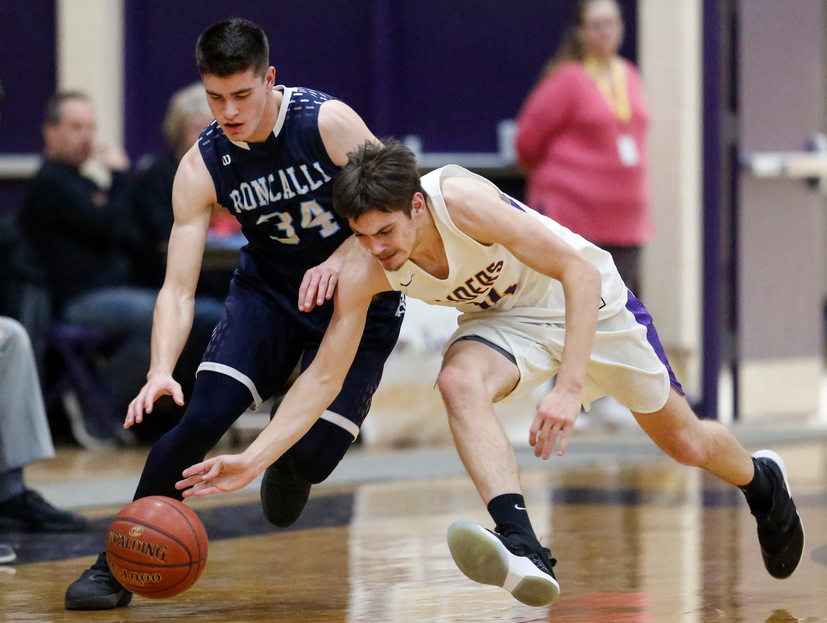 Two Rivers' Trent Van Ess (14) tips the ball away from Roncalli's Ian Behringer (34) at Two Rivers High School Friday, February 1, 2019, in Two Rivers, Wis. Joshua Clark/USA TODAY NETWORK-Wisconsin