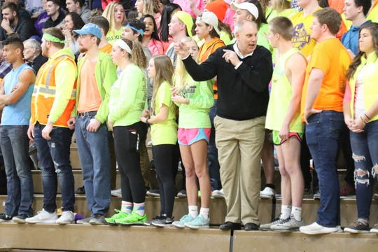 OHSAA commissioner Jerry Snodgrass asks members of the Purple Haze for cheer direction during the Lexington vs Ashland boys basketball game on Friday.