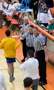 The local officiating crew of, top to bottom, Gary Smith, John Supon and Pat Mulherin fist bump players during pre-game introductions for Mansfield Senior's game Friday night at home against Wooster.