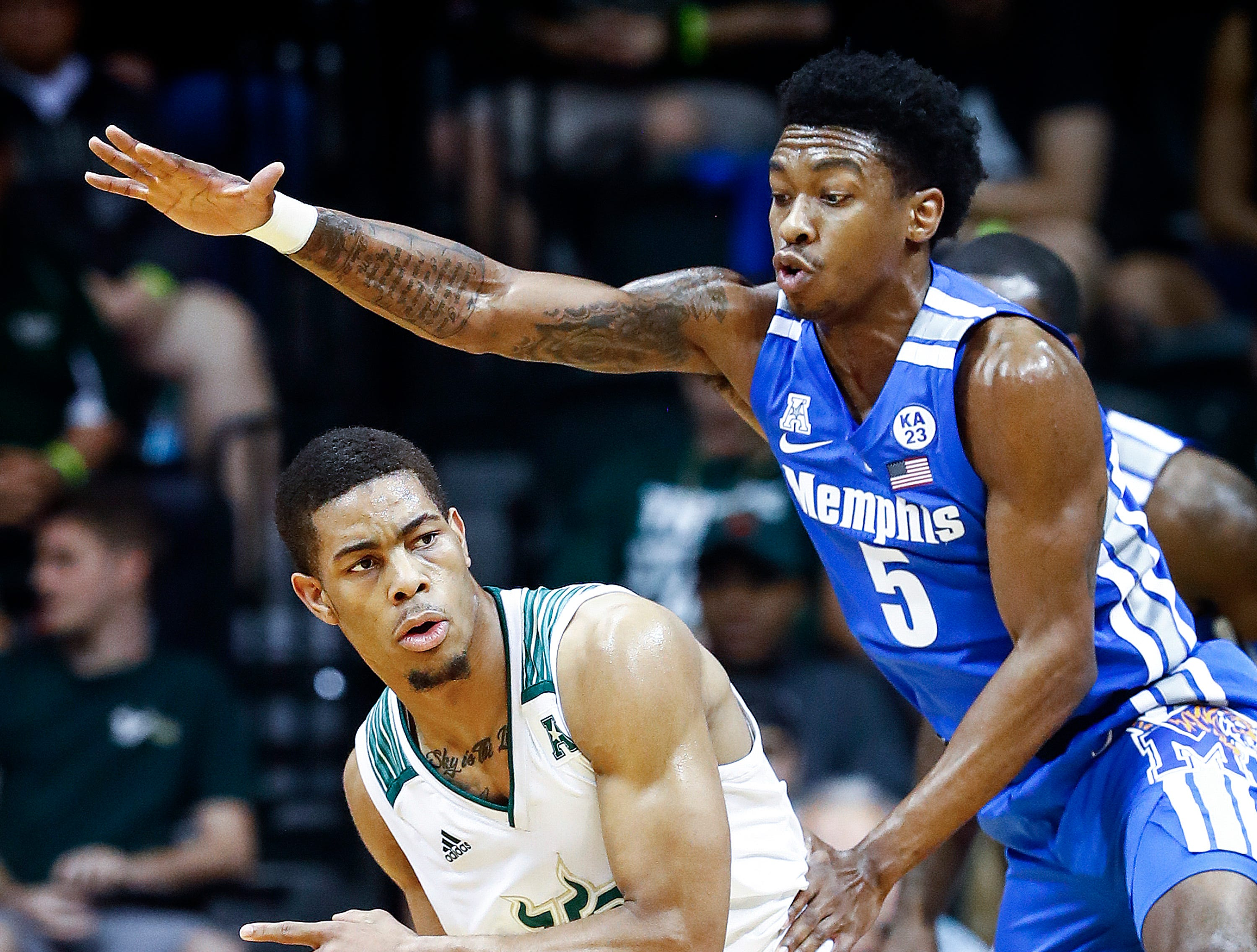 Memphis defender Kareem Brewton Jr. (right) applies defensive pressure to USF guard David Collins (left) during action in Tampa, Saturday, February 2, 2019.
