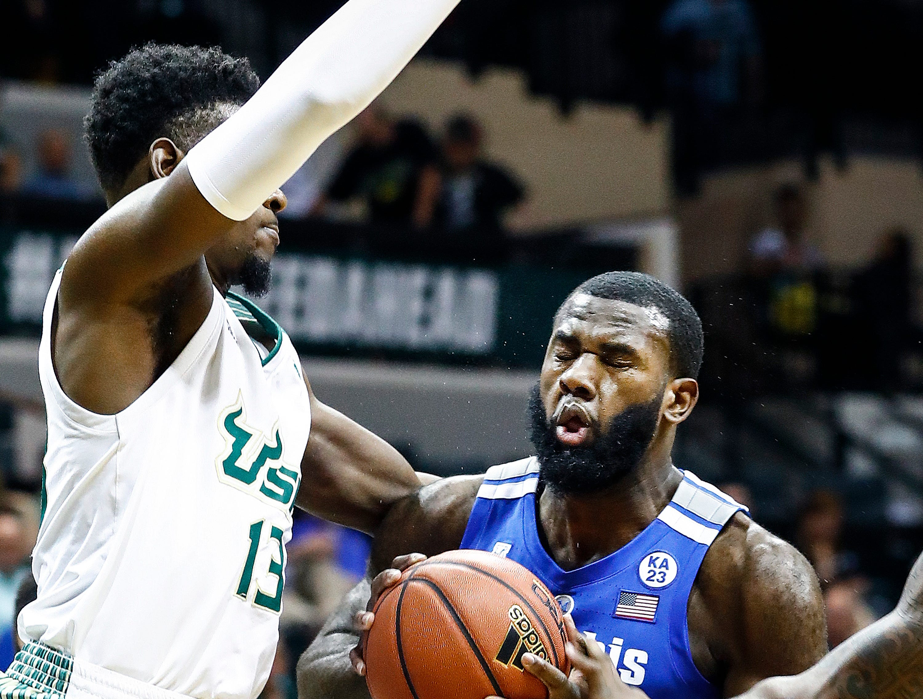Memphis forward Raynere Thornton (right) is fouled while driving the lane against USF defender Justin Brown (left) during action in Tampa, Saturday, February 2, 2019.