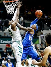 Memphis forward Kyvon Davenport  (right) is called for an offensive foul while driving to the basket against USF defender Alexis Yetna (left) during action in Tampa, Saturday, February 2, 2019.