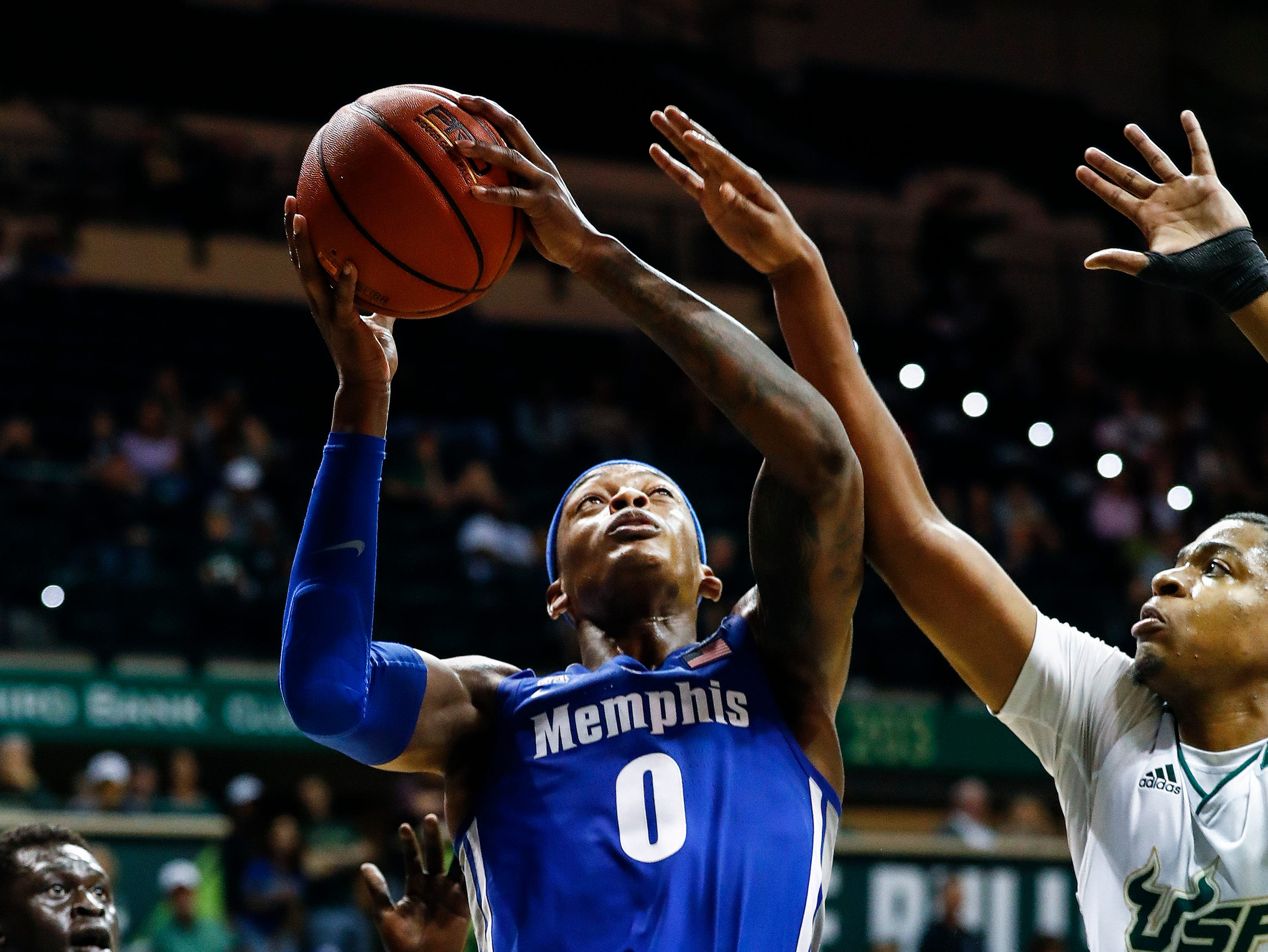 Memphis forward Kyvon Davenport (middle) drives to the basket against USF defender Michael Durr (right) during action in Tampa, Saturday, February 2, 2019.