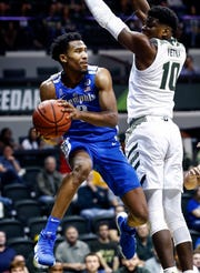 Memphis guard Jeremiah Martin (left) looks to make a pass  around USF defender Alexis Yetna (right) during action in Tampa, Saturday, February 2, 2019.