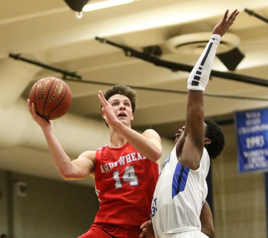 Arrowhead forward Carter Gilmore hangs in the air while putting a shot up over the defense of Waukesha West guard Chris Bready on Feb. 1, 2019.