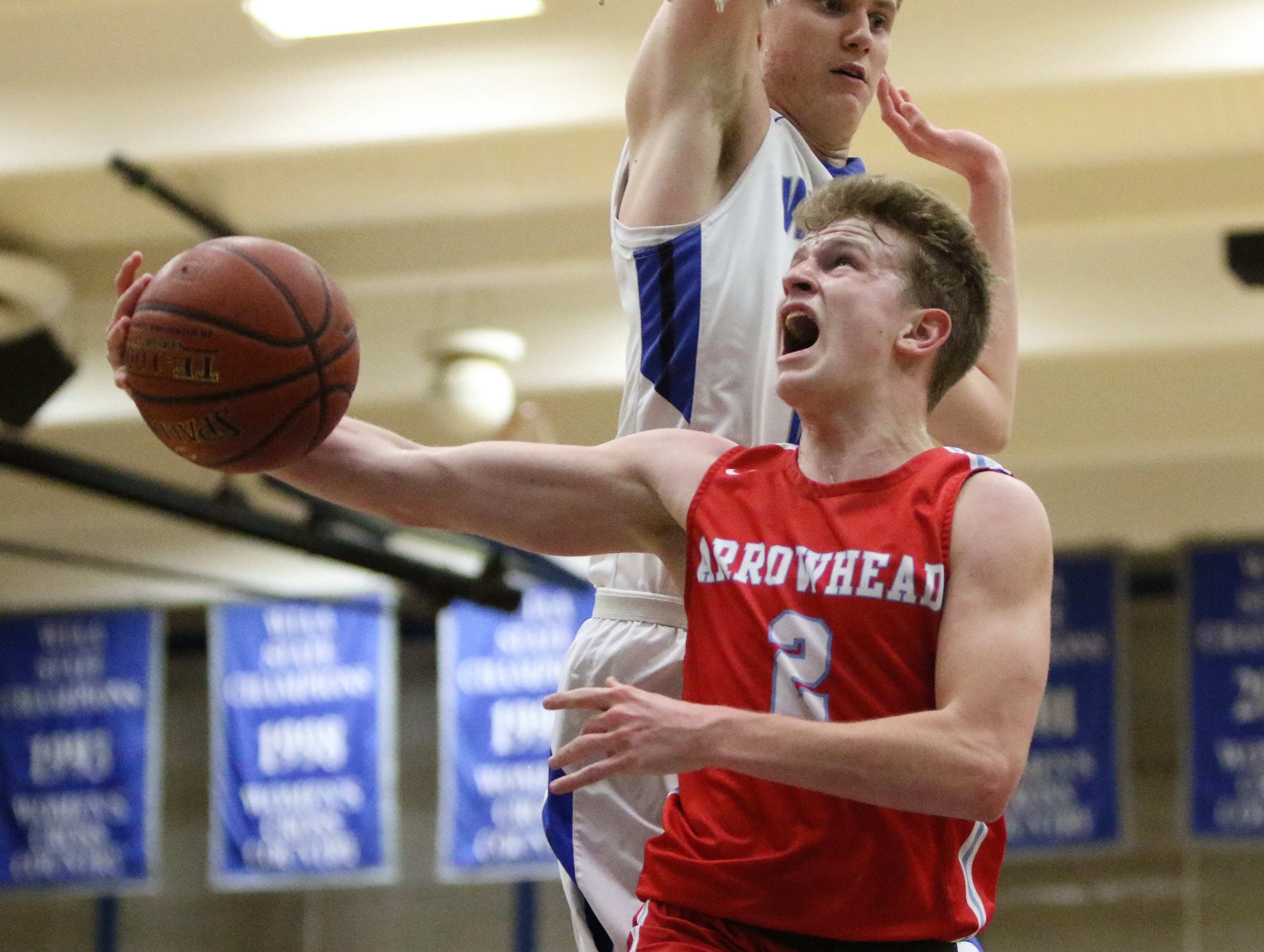 Arrowhead guard Tyler Gouin goes up for a reverse layup as Waukesha West forward David Skogman attempts to block the shot on Feb. 1, 2019.