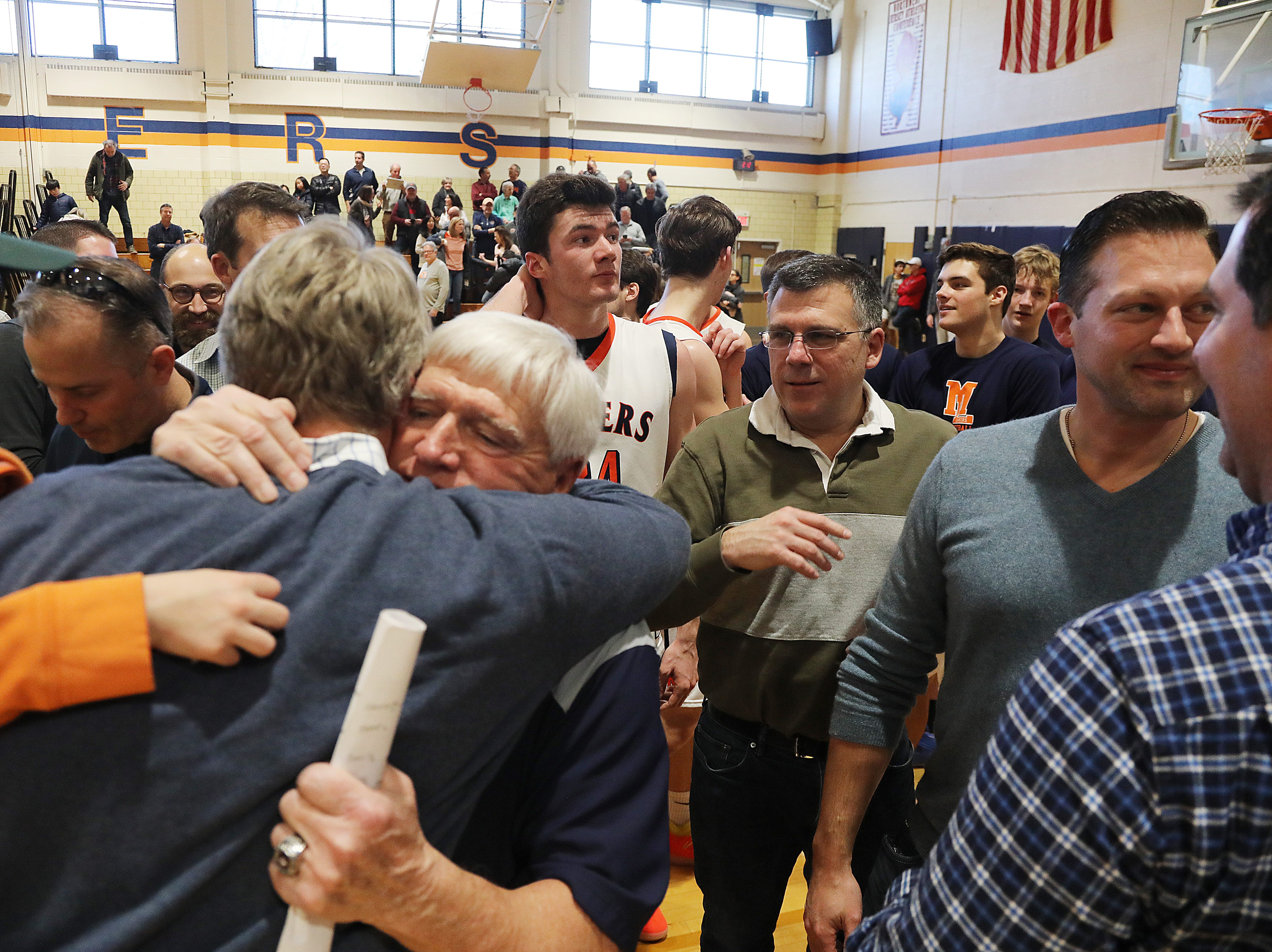 Mountain Lakes head coach John ByDook greets alumni after recording his 500th career win.