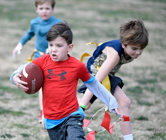 Tyler Gencauski,7, runs with the football during a game of flag football at the 13th annual Father & Son Bowl at the Lasko fields  in Franklin on Sat., Feb. 2, 2019.