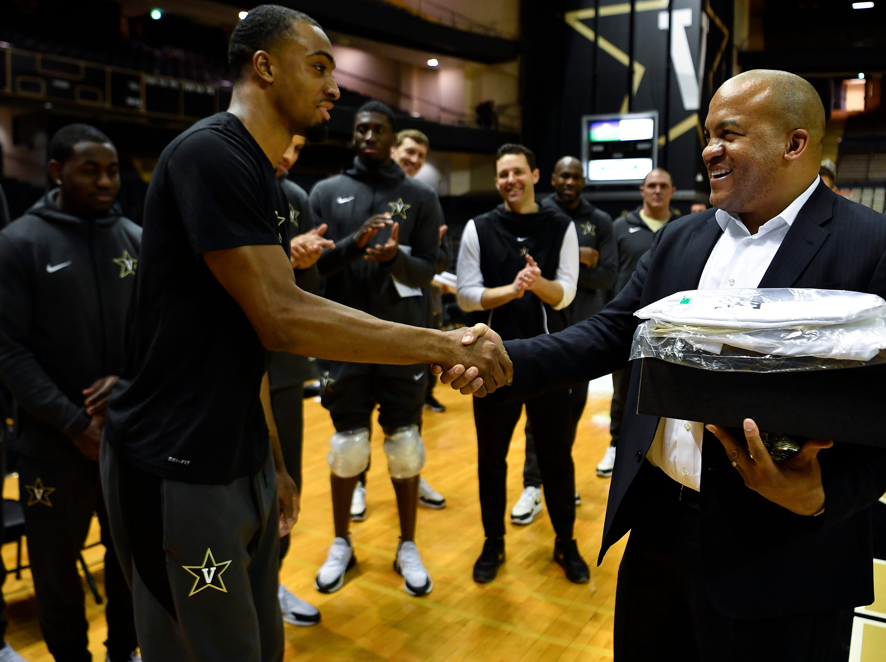 Vanderbilt guard Joe Toye presents new athletic director Malcolm Turner with gifts from the basketball team as he visits different athletic programs during his first day on campus Friday Feb. 1, 2019 in Nashville, Tenn.