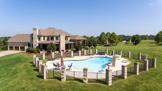 The back of the home, featuring a fenced swimming pool and living area, at 2061 McMahan Hollow Road in Pleasant View.