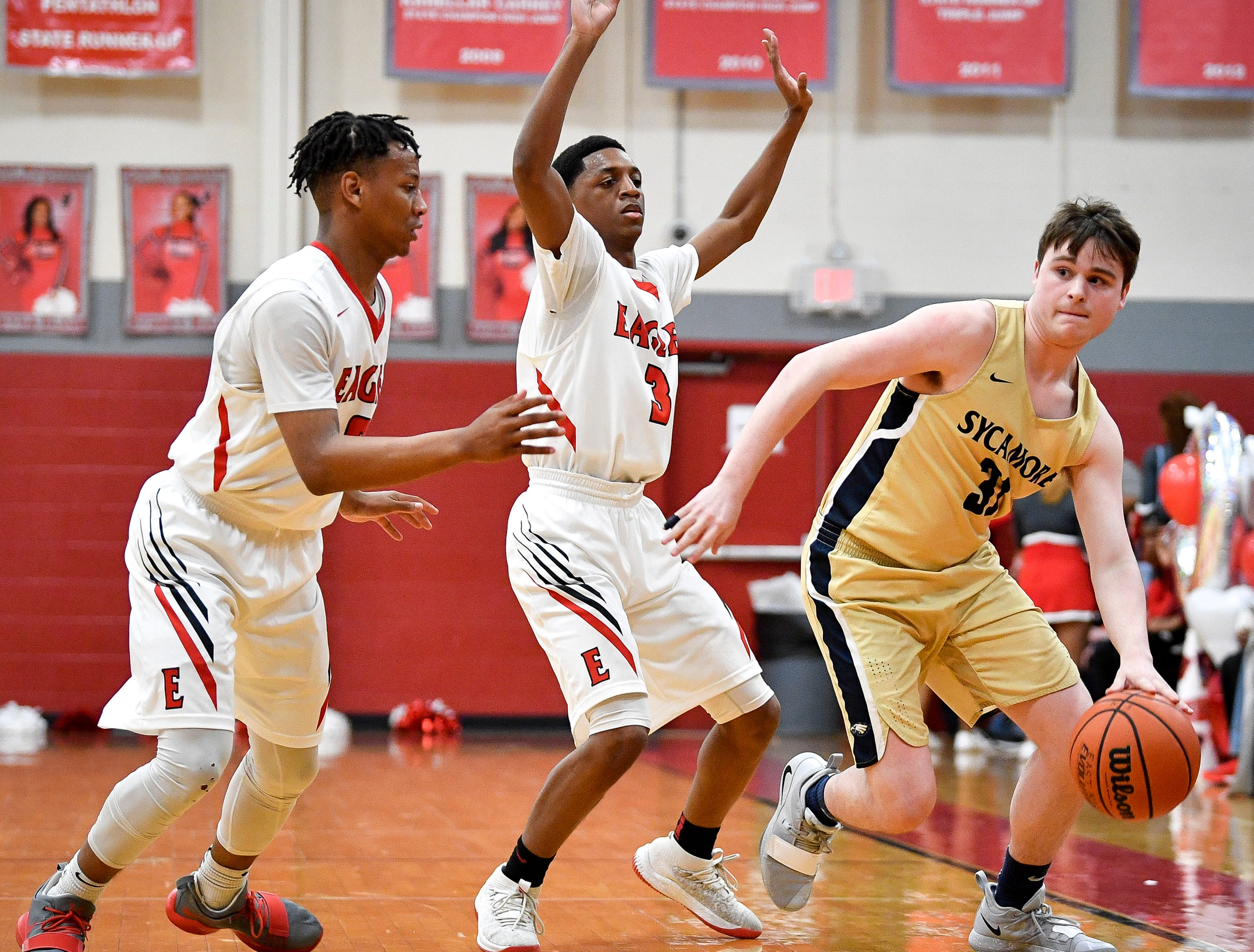 East Nashville's Taras Carter (0) and Caleb Grimes (3) guard Sycamore's Dalton Dutton (31) during the first half at East Nashville Magnet High School in Nashville, Tenn., Friday, Feb. 1, 2019.