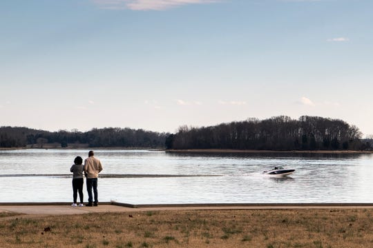 People take in the view as a boat passes by at Percy Priest Lake in Nashville, Tenn., Saturday, Feb. 2, 2019. The temperature reached the low 60s on Saturday afternoon.