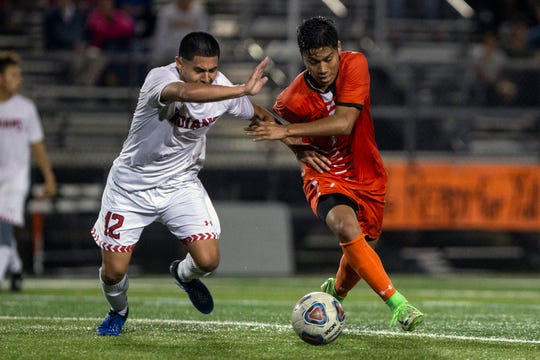 Immokalee's' Gerardo Santana-Cortez (12) and Lely's Alan Garcia chase down the ball in the Class 3A-District 14 boys soccer championship game Wednesday at Lely High School. The Trojans won, 3-1.