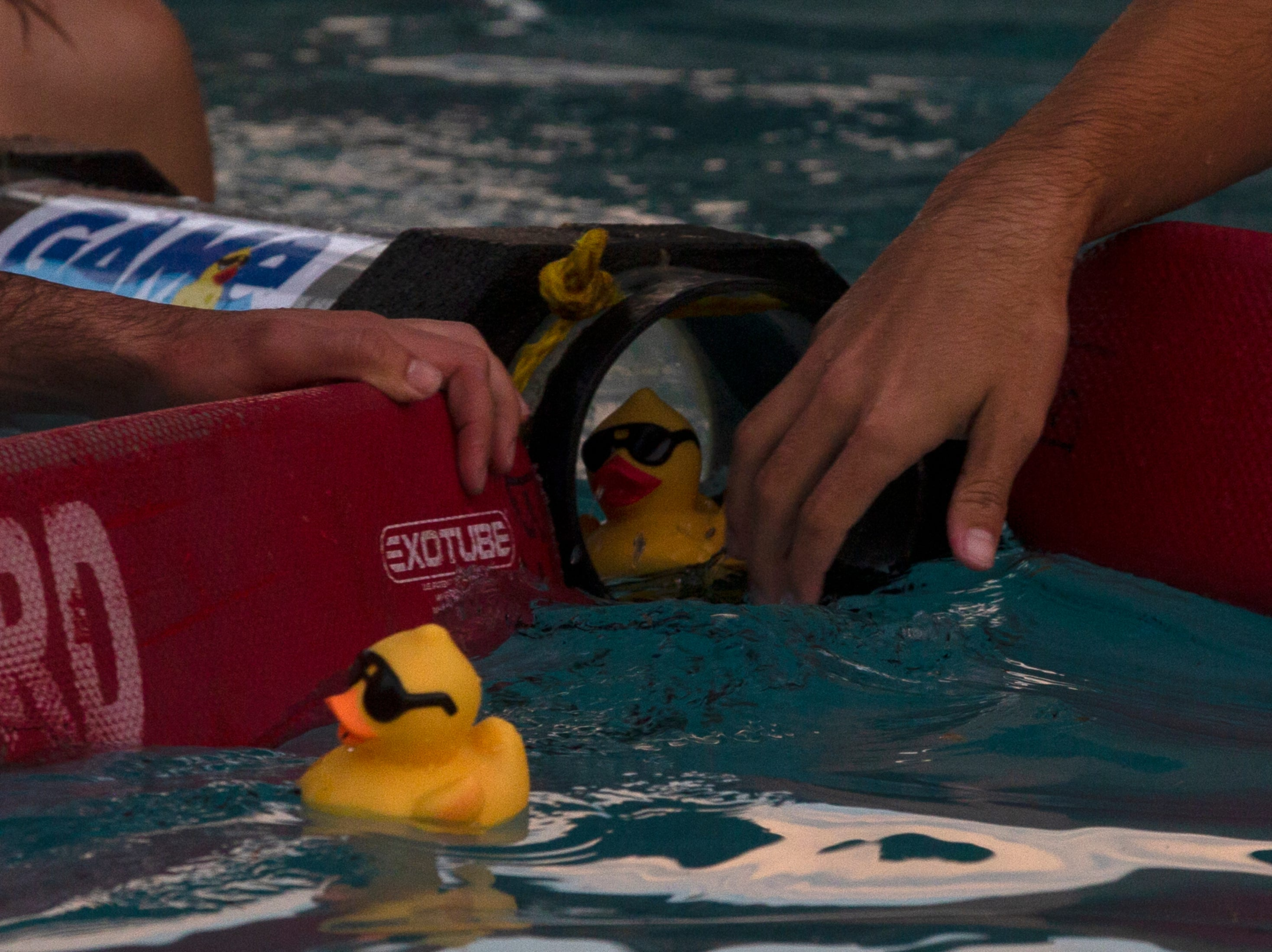 Sun-N-Fun Lagoon lifeguards collect the first and second place ducks during Saturday's Great Naples Duck Race at Sun-N-Fun Lagoon in North Collier Regional Park.