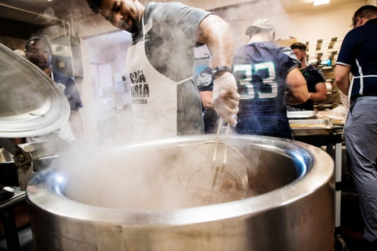 Tyler Claytor, the linebackers coach for Ave Maria University cooks hot dogs in a kettle during the third annual Super Bowl tailgating meal at the Our Lady of Guadalupe Catholic Church in the Casa Maria Soup Kitchen in Immokalee on Friday, Feb. 1, 2019. Coaches and players from Ave Maria University football team cooked and served meals. Casa Maria Soup Kitchen is in need of a new kettle. This one is old and on its last legs.