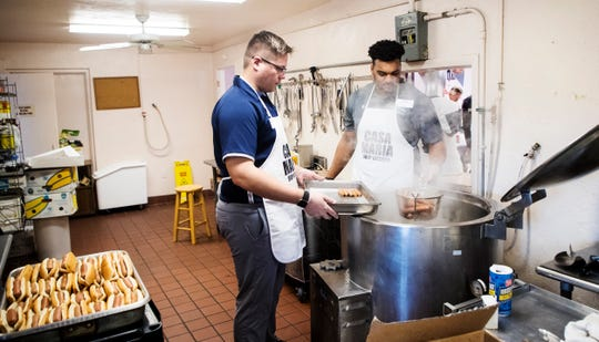 Tyler Claytor, right, the linebackers coach for Ave Maria University, and tight ends coach Tim Ladd cook hot dogs in a kettle during the third annual Super Bowl tailgating meal at the Our Lady of Guadalupe Catholic Church in the Casa Maria Soup Kitchen in Immokalee on Friday, Feb. 1, 2019. Coaches and players from Ave Maria University football team cooked and served meals. Casa Maria Soup Kitchen is in need of a new kettle. This one is old and on its last legs.