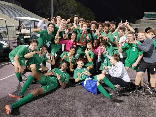 The Fort Myers High School boys soccer team poses with the Class 4A-District 12 championship trophy after beating Palmetto Ridge in the finals on Friday, Feb. 1, 2019.