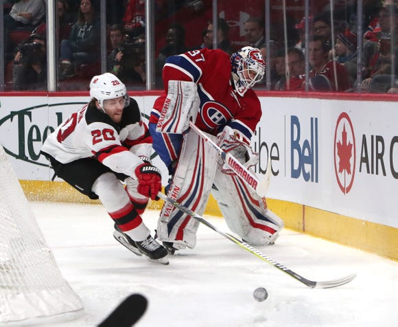 Feb 2, 2019; Montreal, Quebec, CAN; NMontreal Canadiens goaltender Antti Niemi (37) clears the puck next to New Jersey Devils center Blake Coleman (20) during the second period at Bell Centre.