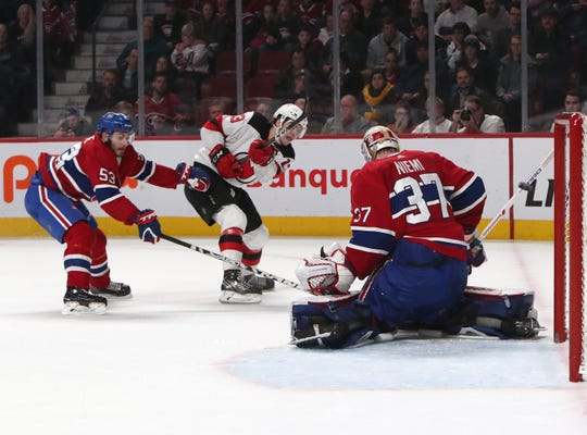 Feb 2, 2019; Montreal, Quebec, CAN; New Jersey Devils center Nico Hischier (13) shoots and scores against Montreal Canadiens goaltender Antti Niemi (37) as defenseman Victor Mete (53) defends during the over time period at Bell Centre.