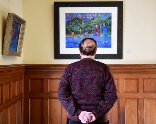 An art reception for the exhibit, Women Dreaming of Doors: Paintings and Prints by Linda Hillringhouse at Passaic County Community College Art Galleries in Paterson, NJ on Saturday February 02, 2019. A man contemplates one of the pieces in the exhibit.