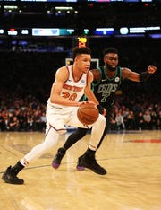Feb 1, 2019; New York, NY, USA; New York Knicks forward Kevin Knox (20) dribbles the ball around Boston Celtics guard Jaylen Brown (7) during the first half at Madison Square Garden.