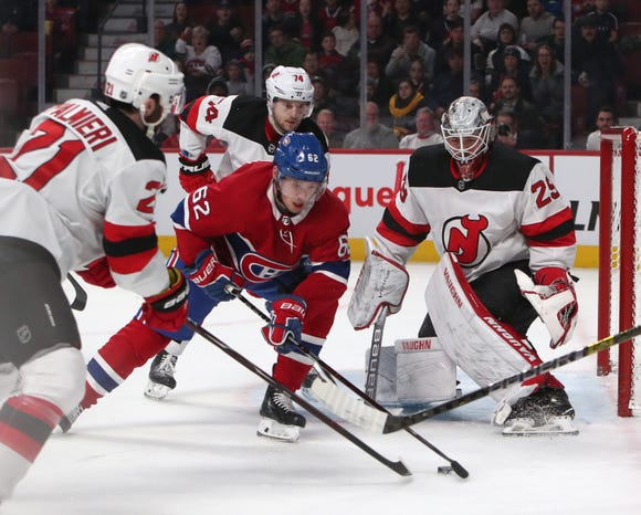 Feb 2, 2019; Montreal, Quebec, CAN; Montreal Canadiens left wing Artturi Lehkonen (62)  plays the puck in front of New Jersey Devils goaltender Mackenzie Blackwood (29) as right wing Kyle Palmieri (21) defends during the first period at Bell Centre.