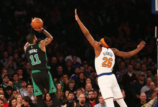 Feb 1, 2019; New York, NY, USA; Boston Celtics guard Kyrie Irving (11) shoots the ball over New York Knicks center Mitchell Robinson (26) during the first half at Madison Square Garden.