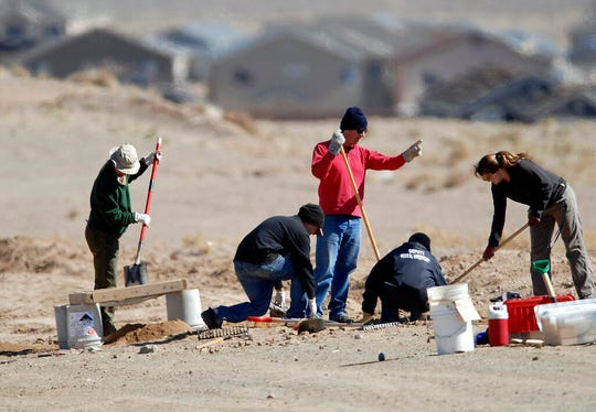 In this Feb. 13, 2009 file photo, crime scene investigators search for human remains in a large expanse of desert in Albuquerque, N.M.