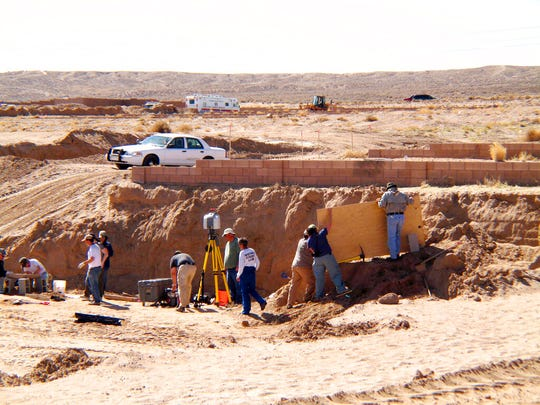 In this Feb. 28, 2009 file photo, forensic experts excavate human remains from an area that had been razed for a housing development in Albuquerque, N.M.