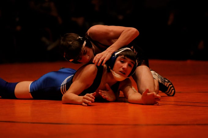 Aztec's Jaren McBride looks to lock up Cedaredge, Colorado's Lane Hunsberger on the ground in the 106-pound division during Friday's wrestling duals in Aztec.