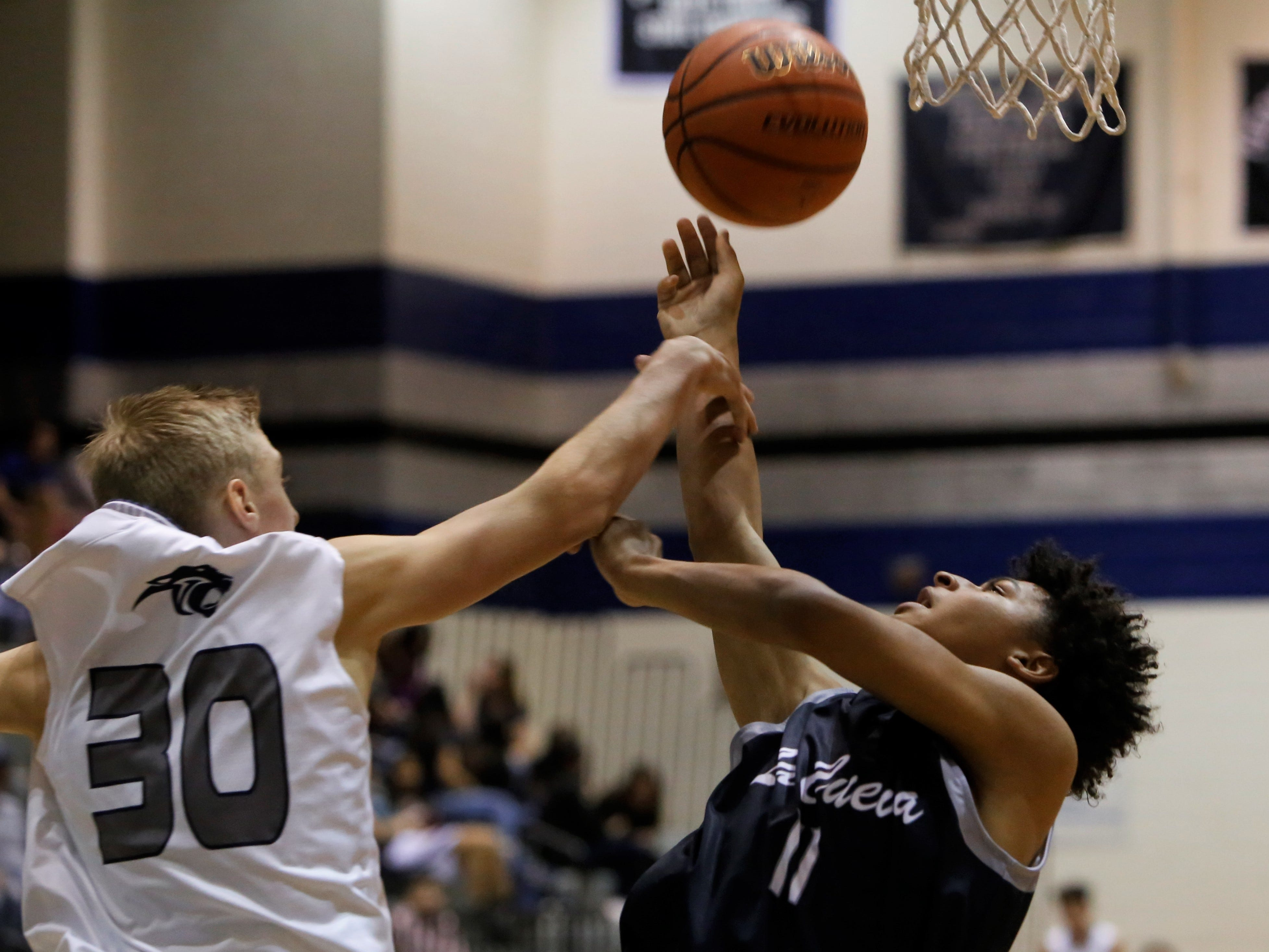 La Cueva's Connor O'Toole drives to the basket and gets fouled by Piedra Vista's Mason Van Ottesen during Saturday's District 2-5A game at Jerry A. Conner Fieldhouse in Farmington.