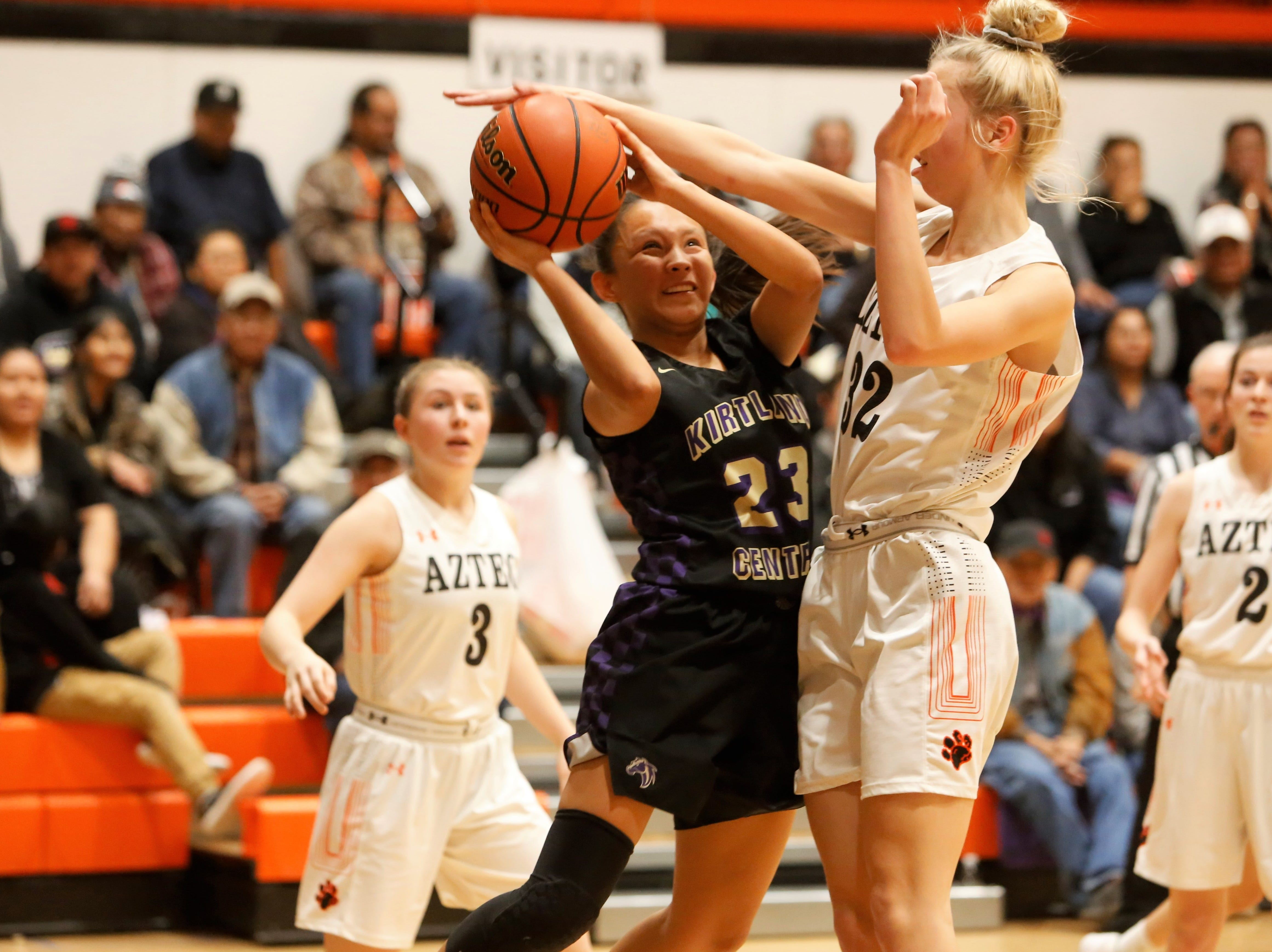 Kirtland Central's Avery Begay attacks the basket and gets fouled by Aztec's Reigan Weaver during Friday's District 1-4A game at Lillywhite Gym in Aztec.