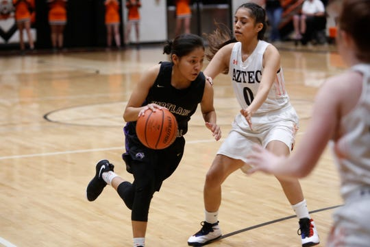 Kirtland Central's Melanie Yazzie drives toward the basket against Aztec's Jay Davis during Friday's District 1-4A game at Lillywhite Gym in Aztec.