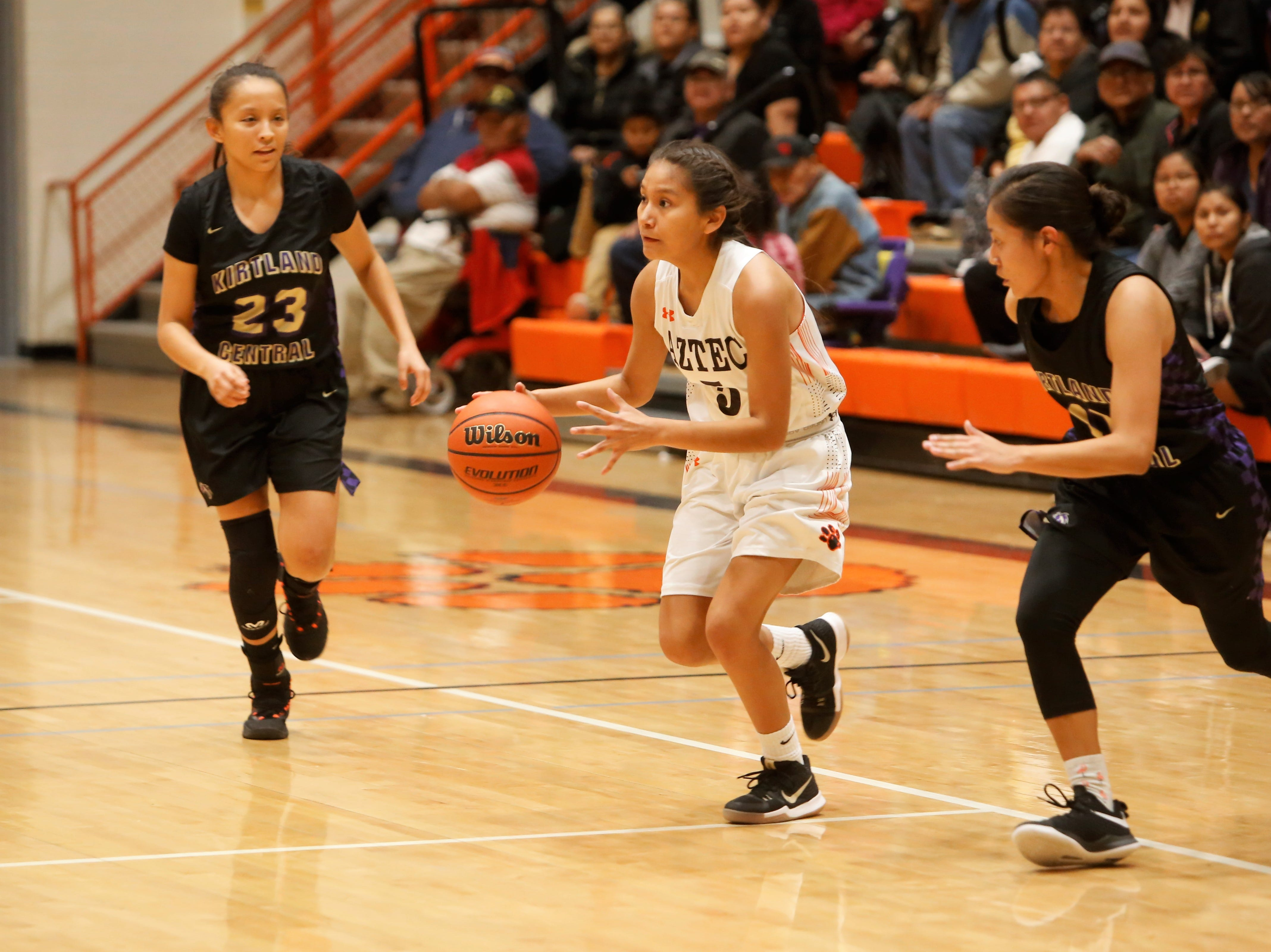 Aztec's DaShauntee Gonzales looks to pass the ball down the right side against Kirtland Central's Avery Begay (23) and Melanie Yazzie (11) during Friday's District 1-4A game at Lillywhite Gym in Aztec.