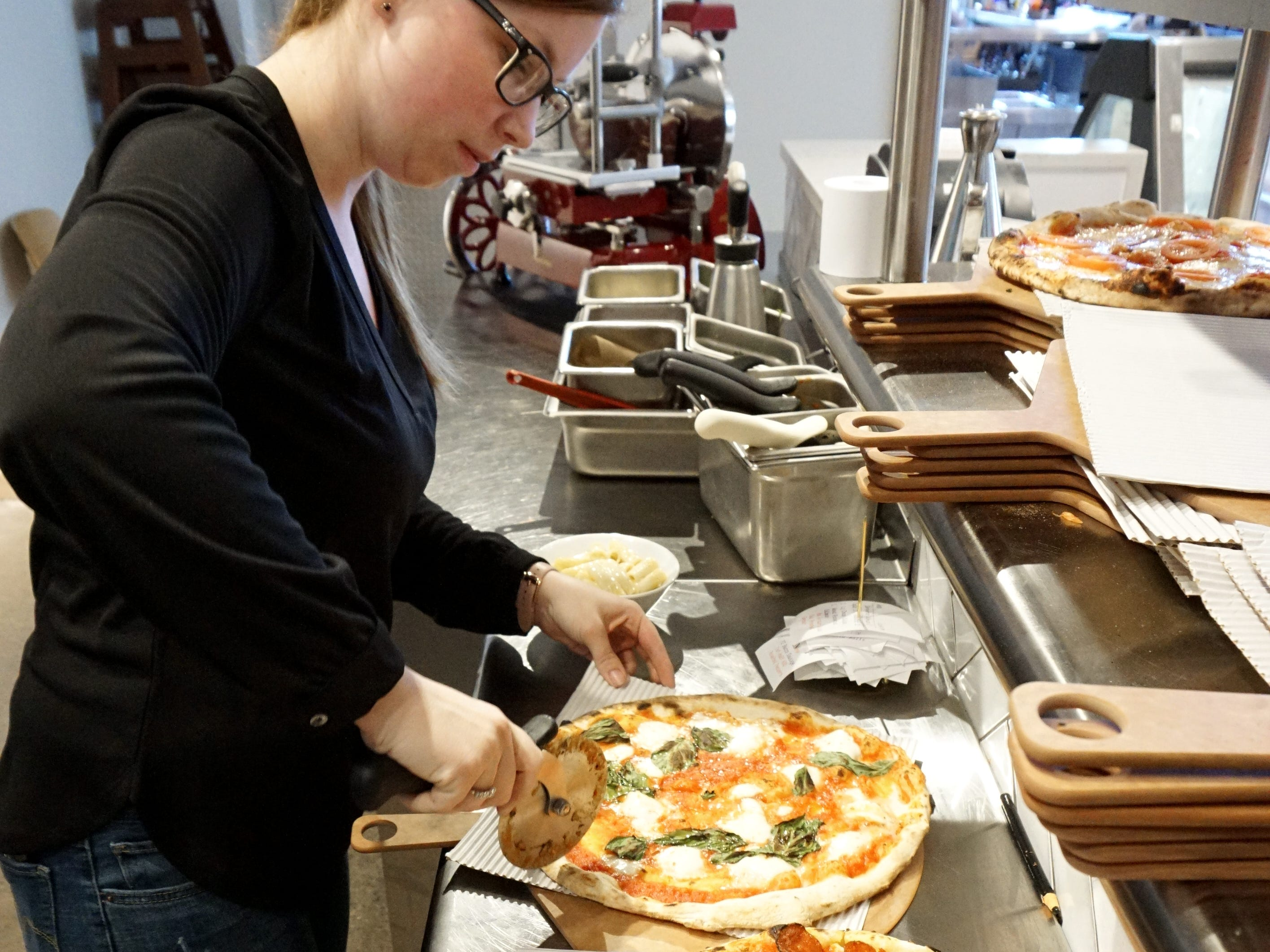 Heather Burleson slices up a couple of pizza for to-go.