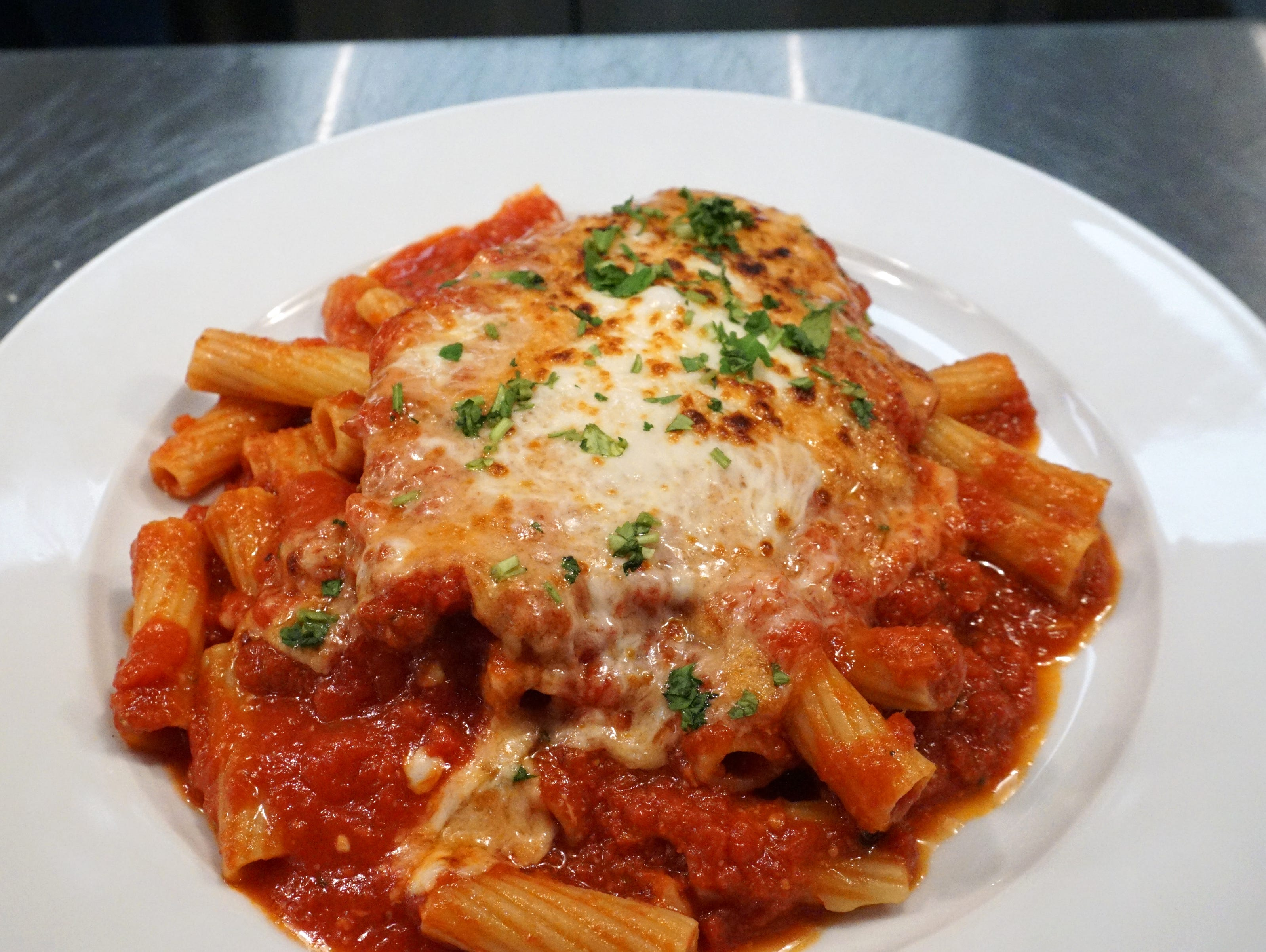 A chicken parmesan on a bed of zitti is readied for a lunch time customer at Plymouth's Bigalora restaurant.