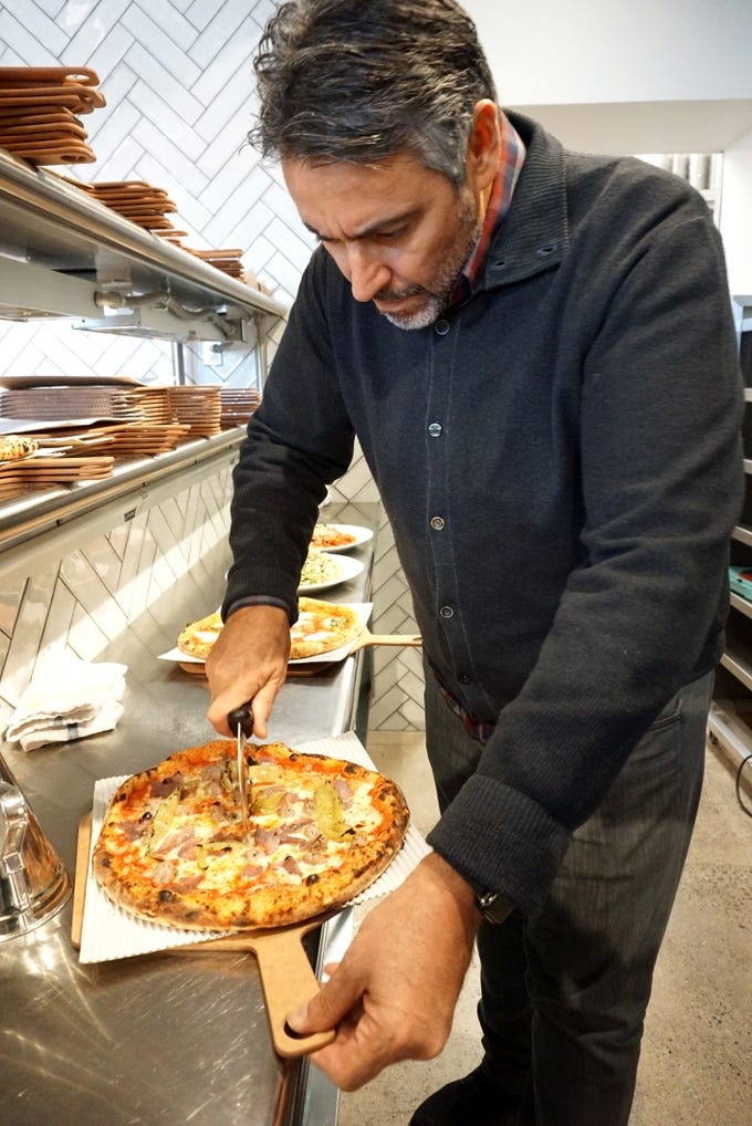 Bigalora co-owner Luciano DelSignore slices up a pizza right out of the Plymouth eatery's oven on Feb. 1.