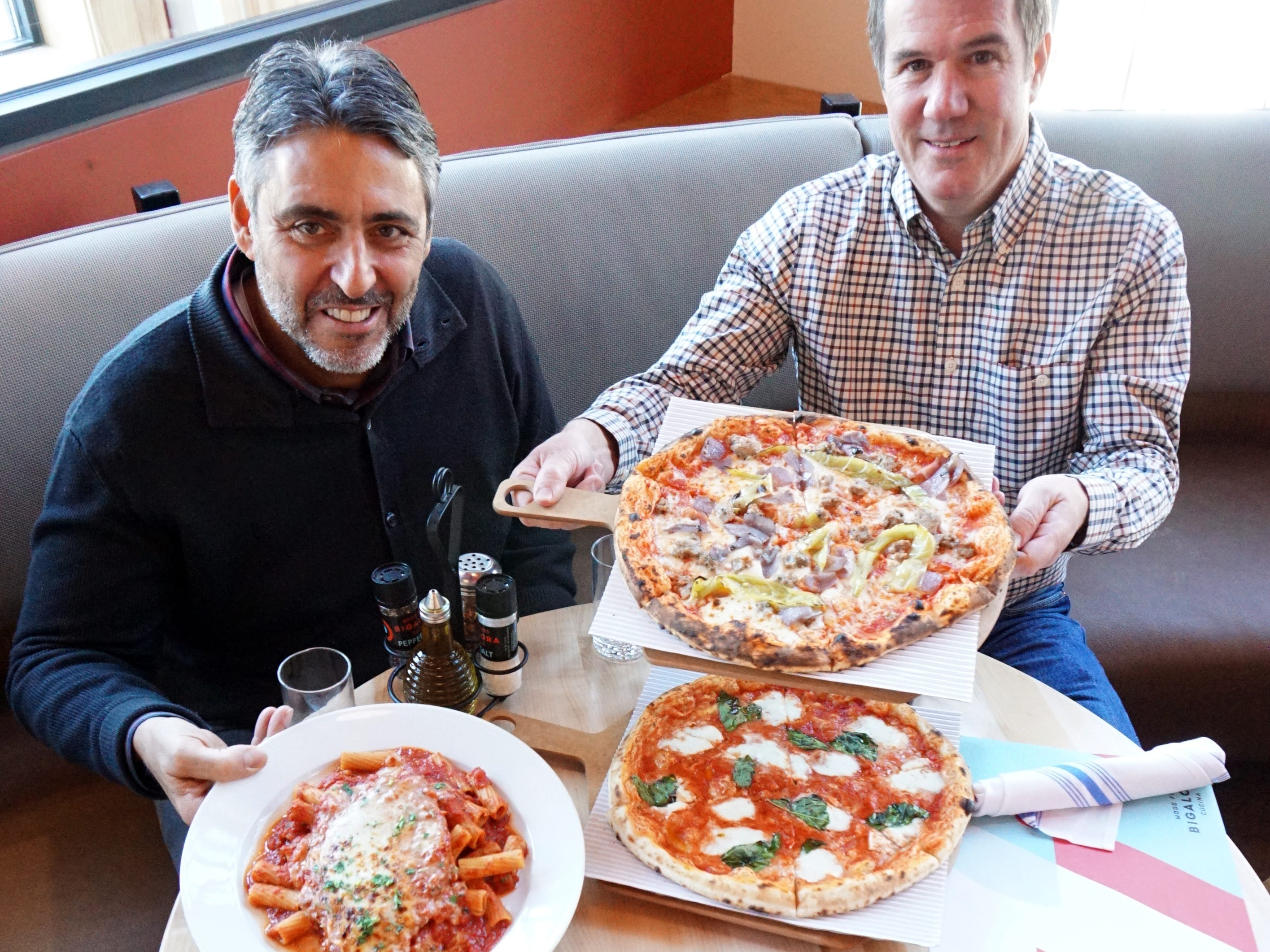 Bigalora co-owners Luciano DelSignore, left, and Mike Collins display some of their downtown Plymouth restaurant's fare including chicken parmesan, a mozzarella and basil and sausage and red onion pizza, and a chopped brussel sprout salad.