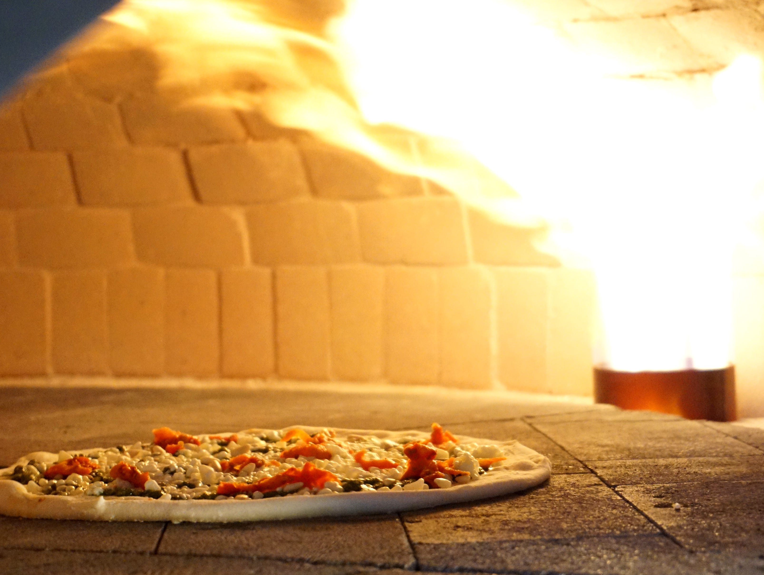 A sundried tomato pizza enters the 900 degree oven at Bigalora on Feb. 1 at lunch time. The oven, with a ceramic base that rotates, is gas-fired and most pizzas make on 90 second circumnavigation of the oven and are ready at that point.